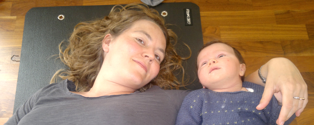 Mum lying down & relaxing with sleeping baby