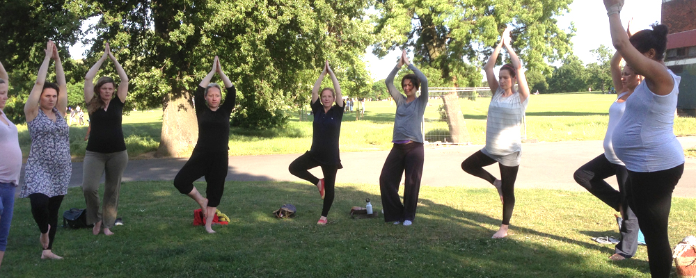 Pregnant women doing Tree Pose outdoors in the sunshine