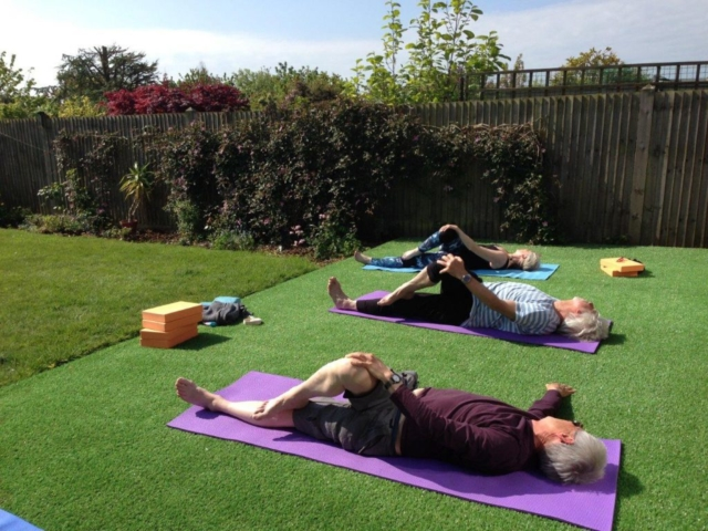 Three senior citizens doing yoga in the garden