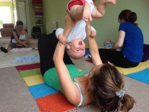 Mum lying on back holding her baby upside down