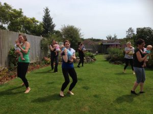 Postnatal mums dancing in the garden with their babies