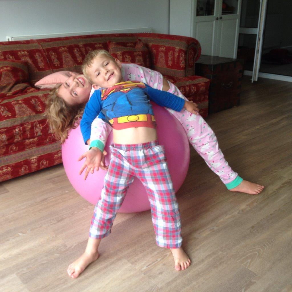 2 children on pink yoga ball