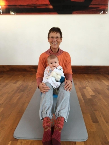 Baby sitting with YogaSue in mum & baby yoga class