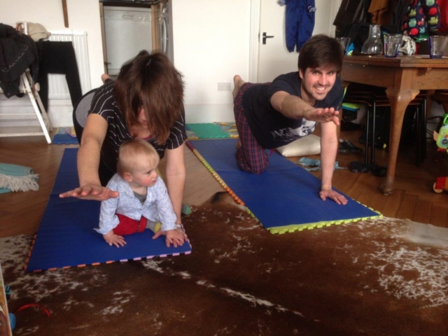 Parents doing yoga with toddler