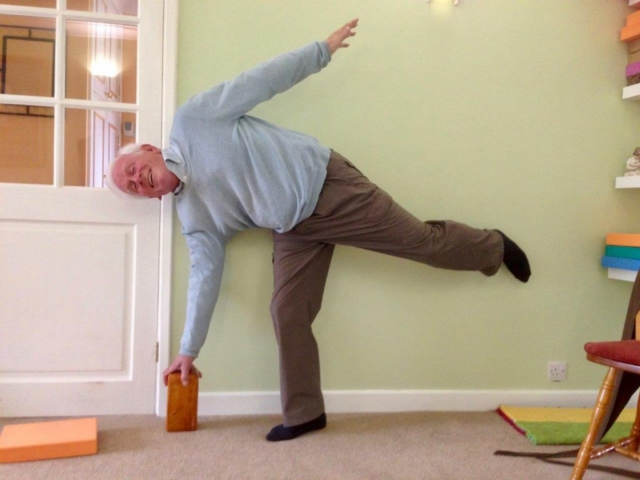 Elderly man balancing on one leg against the wall