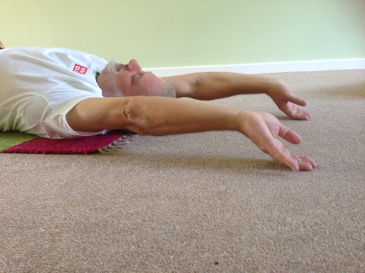 Man stretching arms overhead with fingers to floor