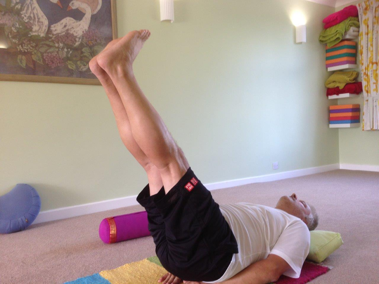Man lying on back lifting 2 legs up together