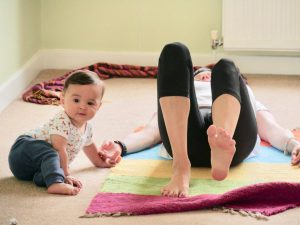 Mum doing yoga in hand contact with baby